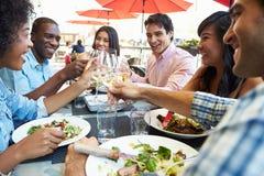 Grupp av vänner som tycker om mål på den utomhus- restaurangen Arkivfoton