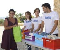 Grupp av volontärer som samlar kläddonationer Royaltyfri Bild
