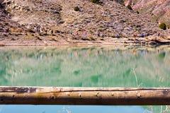 grupp av vuxet folk med den färgrika ryggsäcken som trekking på en bana av sand och stenar som går bredvid en sjö som reflekterar arkivbild