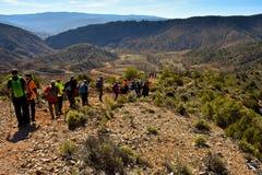 grupp av vuxet folk med den färgrika ryggsäcken som trekking på en bana av sand och stenar som går ner ett berg med förbluffa arkivfoton