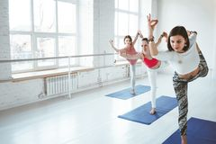 Grupp av vuxna kvinnor som tillsammans gör yogaövningar i konditiongrupp Det aktiva folket övar yoga poserar på mattt royaltyfria foton