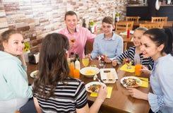 Grupp av vuxna människor och tonåringar som spenderar tid i kafé Arkivbilder