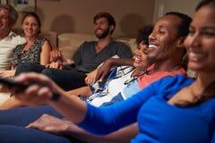 Grupp av vuxna vänner som tillsammans håller ögonen på television Royaltyfria Bilder