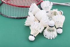 Grupp av worned ut badmintonfjäderboll med racket på domstolen Arkivbild