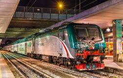 Grupp E lastbilstransport för 464 lokomotiv ett regionalt drev på den Milano Porta Garibaldi järnvägsstationen Royaltyfria Foton