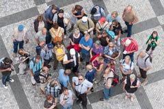 Grupp för bästa sikt av okända turister som väntar på den gamla stadfyrkanten i mitten av Prague, Tjeckien Royaltyfri Bild