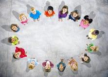 Grupp för flyg- sikt av multietniska ungar i cirkel Arkivfoto