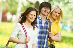 Grupp för tre ung deltagare utomhus Arkivfoton