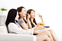 grupp för ung kvinna som äter mellanmål och håller ögonen på tv:n Royaltyfri Foto