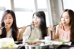 Grupp för unga kvinnor som äter den varma krukan Royaltyfri Foto
