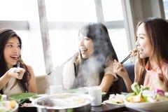 Grupp för unga kvinnor som äter den varma krukan Arkivbilder