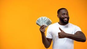 Grupp f?r Afro--amerikan maninnehav av dollar och upp uppvisningstummar, start royaltyfri fotografi