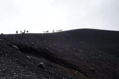 Grupp människor överst av ett berg på Etna Volcano Arkivfoto