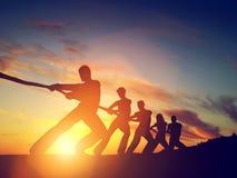 Grupp människor dragande linje för lag som spelar dragkampen