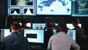 Grupp människor i beskickningen Control Center fyllde med skärmar som firar lyckade Rocket Launch lager videofilmer