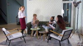 Grupp människor i en vardagsrumstång som är betjänad av en vänlig servitris lager videofilmer