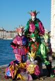 Grupp människor i färgrika dräkter och maskeringar, sikt på Grand Canal Fotografering för Bildbyråer