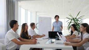 Grupp människor in i kontorskläder på skrivbordet och mentorn nära Whiteboard i affärsmitt stock video
