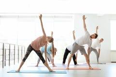 Grupp människor i praktiserande yoga för sportswear arkivfoto