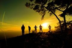 Grupp människor lyckligt fotvandra stå på en klippasida med armar som lyfts upp Arkivfoto