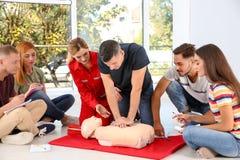 Grupp människor med instruktören som öva CPR royaltyfri foto