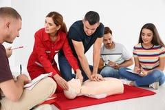 Grupp människor med instruktören som först öva CPR på hjälpmedelgrupp för skyltdocka arkivfoton