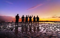 Grupp människor med solnedgånghimmel Royaltyfri Foto