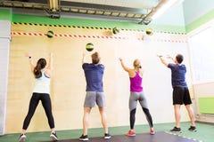 Grupp människor med utbildning för medicinboll i idrottshall Arkivfoton