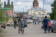 Grupp människor och bilar på huvudvägen i trafik som går till templet - Ryssland Usolye Juli 1, 2017 arkivbild