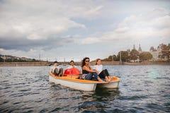 Grupp människor på det pedal- fartyget i sjön royaltyfri foto
