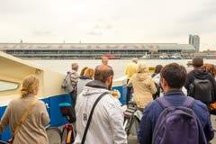 Grupp människor på passagerarfärjaöverskrift in mot centralstationen i Amsterdam, Nederländerna royaltyfri foto