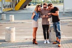 Grupp människor på trottoaren som ser mobiltelefonen royaltyfria foton