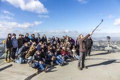 Grupp människor poserar överst av den huvudsakliga tornskyskrapan Arkivbild