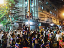 Grupp människor ser pojken klättra en bambuploe i vegetarisk festiv royaltyfria bilder