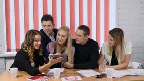 Grupp människor sitter på en tabell som håller ögonen på minnestavlan i attraktiva händer för dam` som ett s ler Vänner håller ög stock video