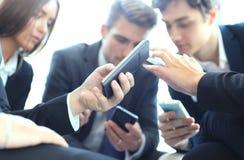 Grupp människor som använder smarta telefoner som sitter på mötet, slut upp på händer royaltyfri fotografi