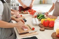 Grupp människor som förbereder kött på matlagninggrupper arkivbild
