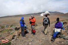 Grupp människor som fotvandrar till överkanten av Mt kilimanjaro Arkivbild