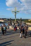 Grupp människor som framme vilar och tar foto av en Kristusstaty i Prague fotografering för bildbyråer