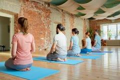 Grupp människor som gör att knäfalla för yoga, poserar på studion Fotografering för Bildbyråer