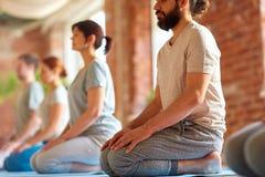 Grupp människor som gör att knäfalla för yoga, poserar på studion Arkivfoto