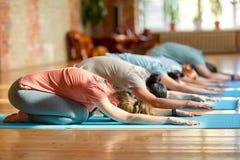 Grupp människor som gör yoga, övar på studion royaltyfri foto