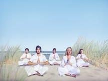 Grupp människor som gör yoga på stranden Arkivbild