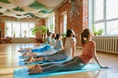 Grupp människor som gör yogakobran, poserar på studion arkivfoto