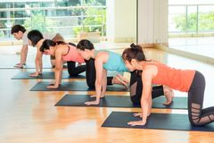 Grupp människor som gör yogatabellöverkanten, poserar i studion som utbildar ro Royaltyfria Bilder
