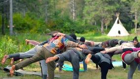 Grupp människor som gör yogayttersidan arkivfilmer