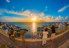 Grupp människor som håller ögonen på förbluffa solnedgång i Tenerife arkivfoton