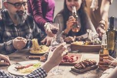 Grupp människor som har att äta middag för målsamhörighetskänsla arkivfoton