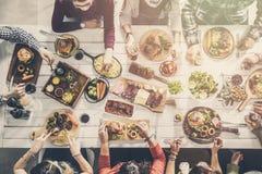Grupp människor som har att äta middag för målsamhörighetskänsla arkivbild