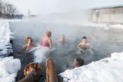 Grupp människor som kopplar av i geotermisk brunnsort i pöl för varm vår Royaltyfri Foto